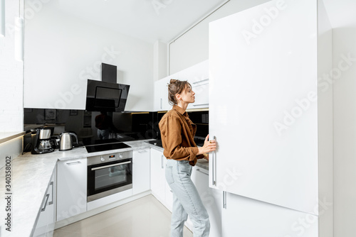 Fényképezés Woman looking into the fridge, standing on the modern kitchen at home