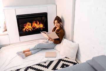 Young woman reading book, relaxing near the fireplace at the modern living room at home