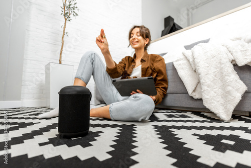 Woman using voice commands to control a smart home devices sitting with a smart speaker and tablet on the floor in the living room
