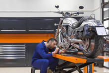 Man Fixing A Motorcycle Raised...