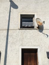 Low Angle View Of Satellite Dish By Window On Old Wall