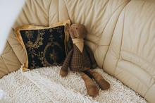 A Soft Toy In The Form Of A Brown, Dressed And Stylish Donkey Sits Alone On A Leather Sofa. Photography, Concept.