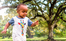 An African American Toddler Is Playing Outside On A Sunny Day