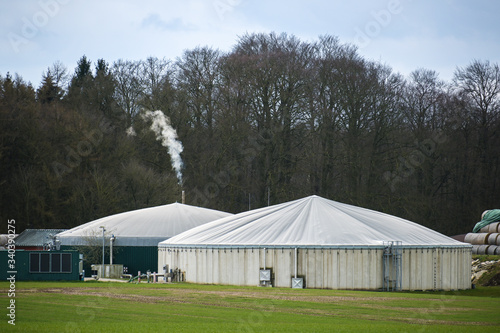 Biogas plant with smoking chimney at the edge of a  forest, cloudy sky, copy spa Canvas Print
