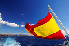Close-up Of Spanish Flag Waving On Ferry Boat In Sea Against Blue Sky