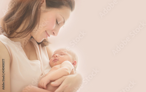 Obraz Mother and her Newborn Baby together. Love. Happy Mother and Baby kissing and hugging. Soft image of Beautiful Family. Maternity concept. Parenthood. Motherhood, adoption concept. On pink background - fototapety do salonu