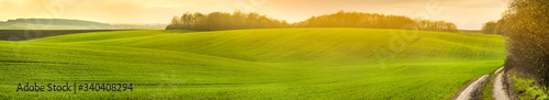 Fotografia panoramic view of farmland in hilly countryside at sunset in spring