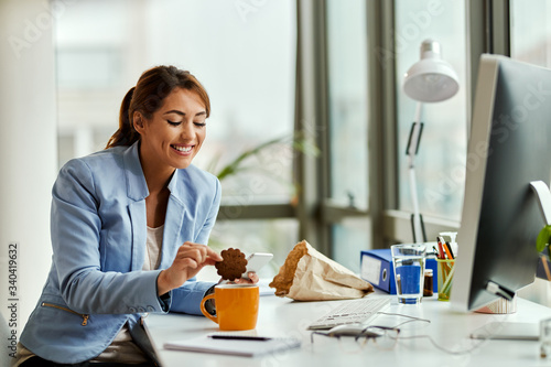 Young businesswoman eating cookie on a break in the office. Wallpaper Mural