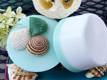 High Angle View Of Homemade Soap With Seashells And Pebble On Metal Grate