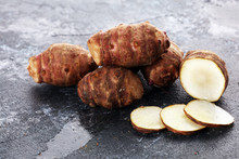 Jerusalem Artichoke And Slices On Rustic Background. Fresh Raw Organic Topinambur