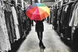 Low Section Of Woman With Colorful Umbrella At Clothing Store