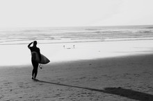 Rear View Of Woman Carrying Surfboard At Beach Against Clear Sky