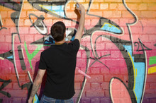 Young Graffiti Artist With Backpack And Gas Mask On His Neck Paints Colorful Graffiti In Pink Tones On Brick Wall. Street Art And Contemporary Painting Process