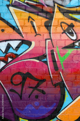 Abstract colorful fragment of graffiti paintings on old brick wall. Street art composition with parts of unwritten letters and multicolored stains. Subcultural background texture © mehaniq41
