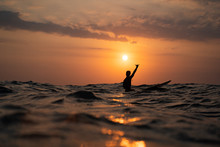 Silhouette Of A Man Surfing At...