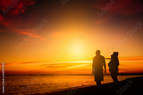 Vászonkép Silhouette family happy on the beach in sunrise or sunset