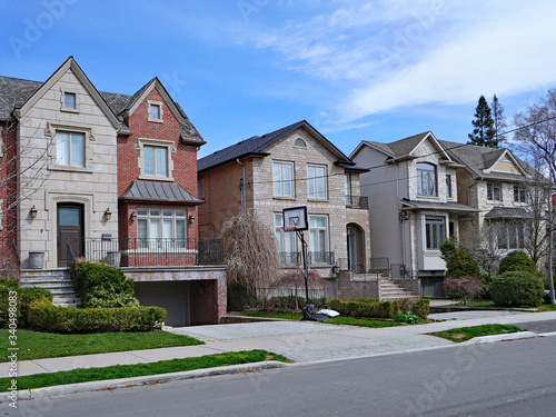 Photo Suburban street with large detached houses with gables