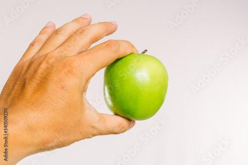 Tela Cropped Hand Of Man Holding Fresh Granny Smith Apple Against White Background