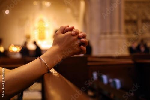 Canvastavla Closeup of woman's hands praying on church bench, coronavirus, copy space