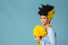 Portrait Of A Very Happy Young Woman In Blue Holding Bouquet Of Fresh Yellow Daffodils Looking To Side