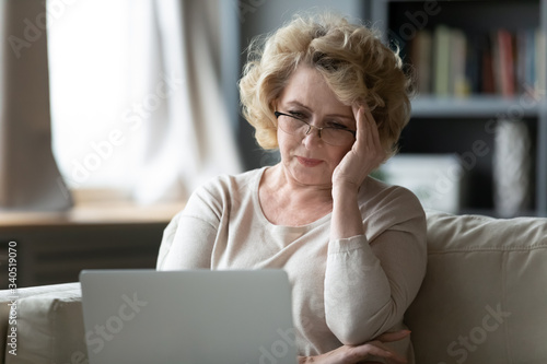 Fotomural Old woman sit on couch using laptop looks at screen feels stressed not understan
