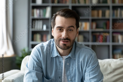 Fototapeta Head shot millennial guy sit on sofa in living room makes video call looks at camera, conversation by distant videocall, distance hiring job interview process, tutor and trainee study on-line concept obraz