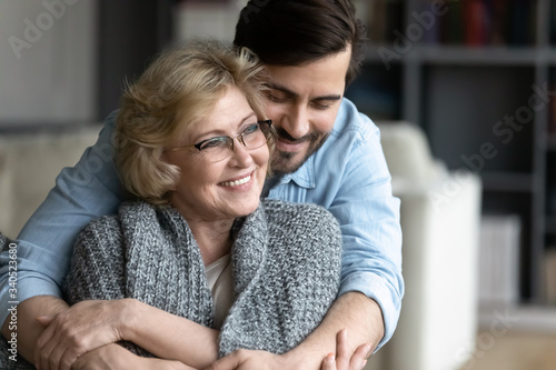 Happy senior mother spend time with grown up son, relatives people hugging at ho Canvas Print