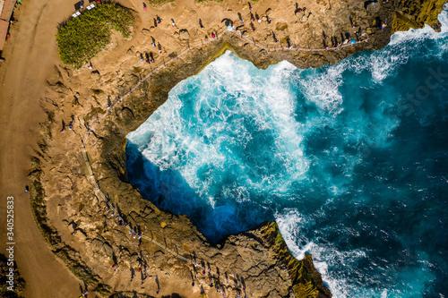 Aerial drone view of people gathering to watch huge ocean waves breaking against Canvas Print
