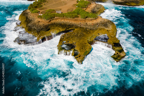 Aerial view of huge ocean waves crashing into a rocky coastline on a tropical is Canvas Print