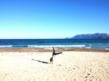 Side View Of Girl Doing Handstand At Beach Against Clear Blue Sky