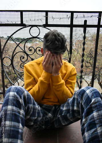 Young man desperate for confinement due to coronavirus sitting on balcony Canvas Print