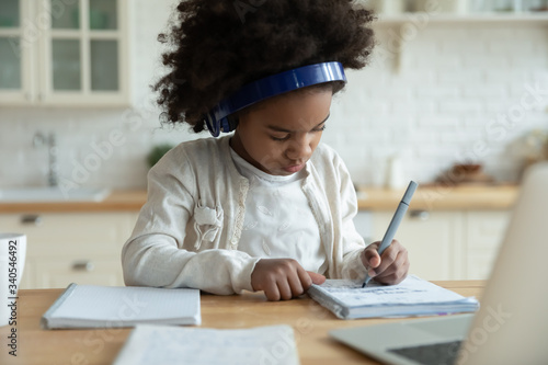 Valokuvatapetti Smart little African American girl in headphones watch online video lesson at ho