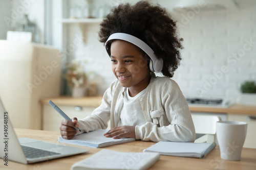 Obraz Smiling small African American girl in headphones watch video lesson on computer in kitchen, happy little biracial child in earphones have online web class using laptop at home, homeschooling concept - fototapety do salonu