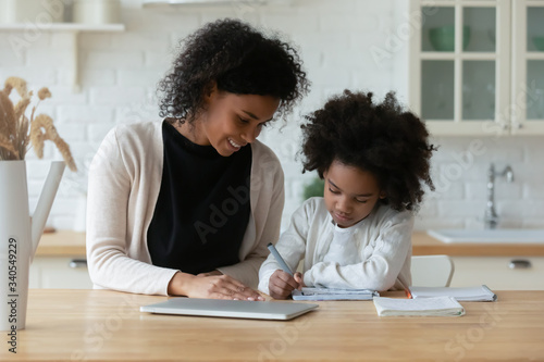 Fényképezés African American young mother and little daughter sit at desk in kitchen studyin