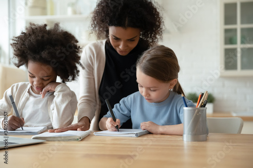 Young African American mother help multiracial daughters with homework, study to Tapéta, Fotótapéta