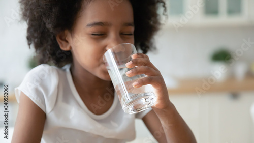 Canvas Print Cute little African American girl drink clean still mineral water from glass at