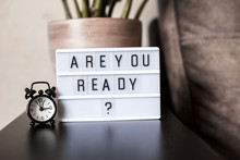 A Room Flower, Standing On The Back Of A Sofa, A Clock And A Light Box With Words Are You Ready.