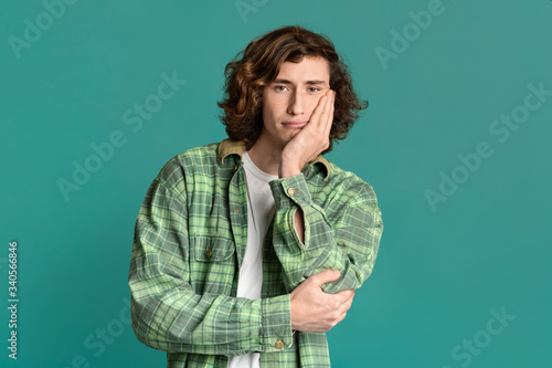 Photographie Attractive millennial guy feeling bored or tired on color background