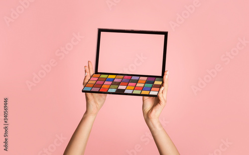 Fotografia, Obraz Unrecognizable woman holding eyeshadow palette on pink background, closeup