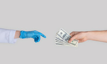 Unrecognizable Patient Giving Money To Doctor In Rubber Glove, Closeup Of Hands