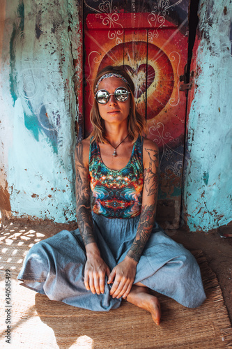 Cuadros en Lienzo A girl in round glasses, a blue skirt and a psychedelic shirt in the form of a h