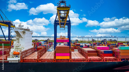 Fototapeta Quay crane, Crane of container terminal in industrial sea port, Sea cargo port with container ship and crane with blue sky background, Business logistic import export transportation by cargo vessel