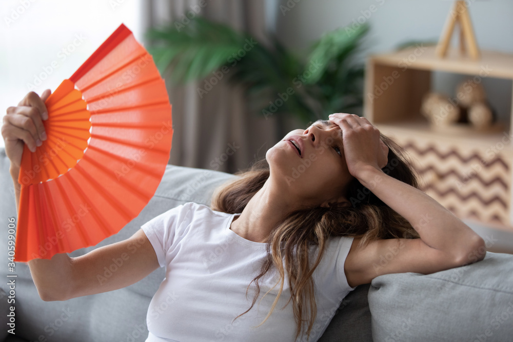 Fototapeta Overheated woman sitting on couch, waving orange paper fan close up, girl feeling unwell, suffering from heating at home, feeling discomfort, hot summer weather or fever, sitting on couch alone