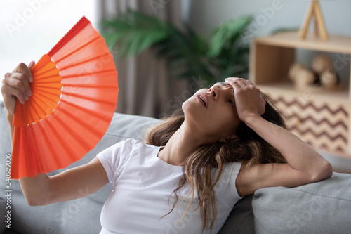 Fotografía Overheated woman sitting on couch, waving orange paper fan close up, girl feelin