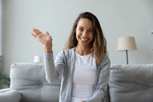 Happy Young Woman With Toothy Smile Waving Hand, Looking At Camera, Sitting On Couch At Home, Vlogger Recording Webinar, Using Webcam, Chatting Online, Making Video Call, Remote Job Interview