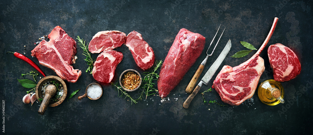 Fototapeta Variety of raw beef meat steaks for grilling with seasoning and utensils