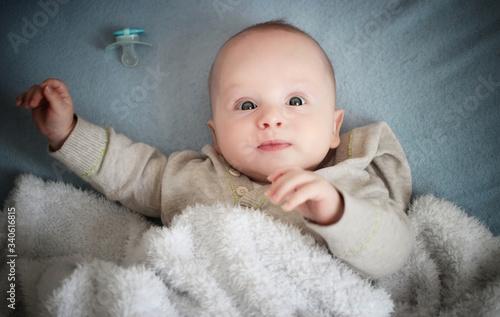 Photo infant baby in blanket, dummy