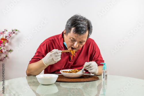 Photo Conceptual of Asian man with face mask, glove and sanitizer dining with ample so