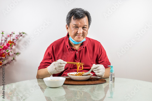 Conceptual of Asian man with face mask, glove and sanitizer dining with ample so Canvas Print