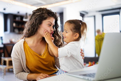 Photo Mother at home trying to work with child distracting her